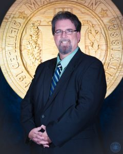 Photo of Michael Drummey standing in a suit with the official Malden seal behind him.