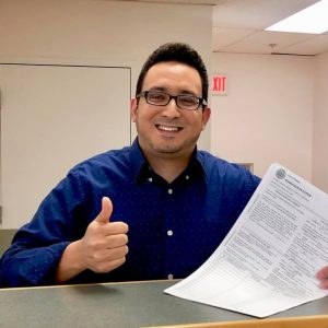 Adam Weldai in a long-sleeved blue shirt seated at a table. His right hand is giving the thumbs-up sign and his left hand is holding a document.
